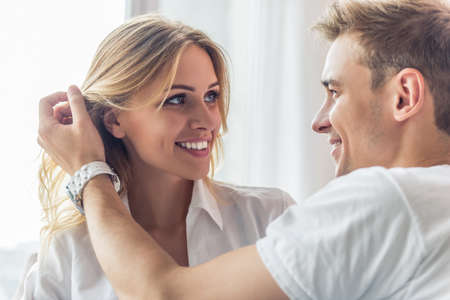 Portrait of beautiful young couple looking at each other and smiling while sitting at home. Man is smoothing his girlfriends hair