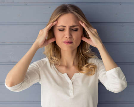 Portrait of beautiful tired young woman having headache, massaging her temples, against gray wall Stock Photo
