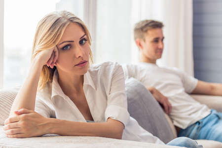 若いカップルの争いです。美しい若い女性は悲しい、自宅でソファに座っている、彼氏はバック グラウンドで座っています。