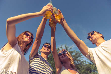 Low angle view of young beautiful people in sun glasses clinking bottles of beverage and smiling while resting outdoors Stock Photo