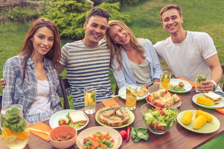 Junge schöne Menschen in die Kamera suchen und lächelt, während am Tisch sitzen und im Freien Picknick