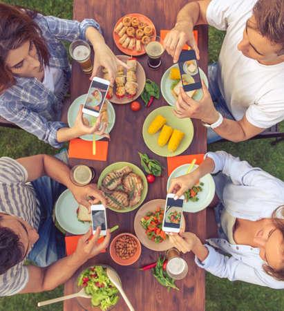 Draufsicht auf junge schöne Menschen, die Fotos von ihrem Essen beim Sitzen am Tisch und Picknick im Freien