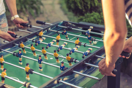 foosball: Cropped image of young people playing foosball while resting outdoors Stock Photo