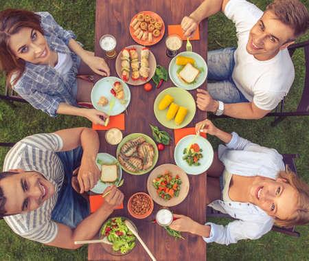 俯视图的年轻美丽的人吃着美味的食物,看着镜头,微笑着坐在桌子上和户外野餐