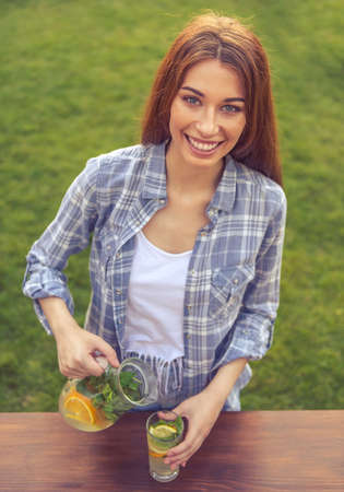 a jar stand: Portrait of beautiful young girl pouring lemonade, looking at camera and smiling while standing outdoors