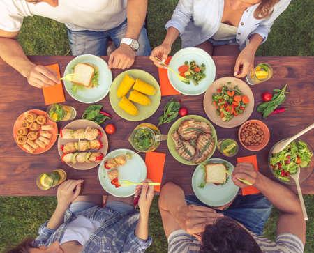 Bovenaanzicht van jonge mooie mensen heerlijk eten tijdens de vergadering op de tafel en met picknick buitenshuis, bijgesneden Stockfoto