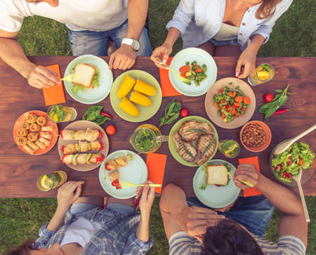 Top view of young beautiful people eating delicious food while sitting at the table and having picnic outdoors, cropped
