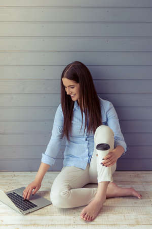 Beautiful young business woman in classic wear is using a laptop, holding a cup of coffee and smiling, sitting barefoot on the floor in front of gray wall