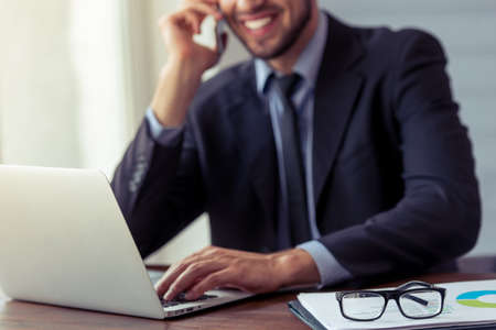 Cropped image of handsome young businessman in formal suit talking on the mobile phone, using a laptop and smiling while working in office Stock Photo
