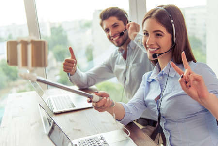 gesturing: Beautiful young business people in headsets are making selfie using phone and monopod, gesturing and smiling while working in office