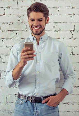 financier: Handsome young businessman in classic shirt is using a smartphone and smiling, standing in front of white brick wall