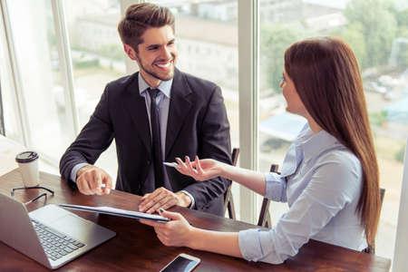 empleados trabajando: Hermosa mujer de negocios joven y apuesto hombre de negocios en trajes formales están usando un ordenador portátil, hablando y sonriendo mientras se trabaja en la oficina