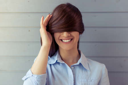 wall covering: Portrait of beautiful young woman covering eyes with her hair and smiling, standing in front of gray wall
