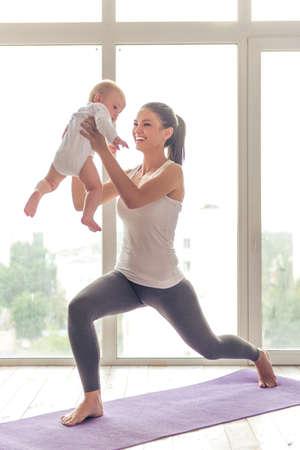 スポーツ ・ ウェアの美しい若いお母さんはウィンドウに対するマットの上彼女の魅力的な小さな赤ちゃんと一緒にヨガをしながら笑っています。