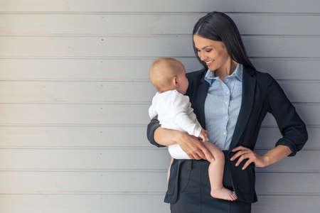クラシックなスーツと彼女の甘い小さな赤ちゃん互いを見ると灰色の壁の前に立って笑顔で美しい女性の肖像画
