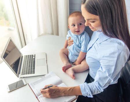 かわいい小さな赤ちゃんを抱いて、ノート作りや office で作業しながら笑みを浮かべて美しいビジネス女性の高角度のビュー。彼のお母さんに赤ちゃ