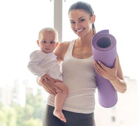 Portrait of beautiful young mom in sports wear holding her charming little baby and yoga mat, looking at camera and smiling while standing against window Zdjęcie Seryjne