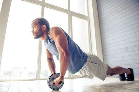ハンサムなアフロ アメリカンのスポーツマンは ab ホイール] ロールアウトで運動をして、自宅で作業しながら楽しみ
