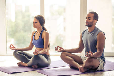 Beautiful Afro American couple in sports clothes is meditating sitting in lotus position on mat while doing yoga at home Stock Photo