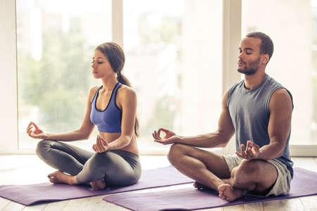 Schöne Afro-amerikanische Paar in Sportkleidung meditiert im Lotussitz auf der Matte sitzen, während die zu Hause Yoga tut Standard-Bild