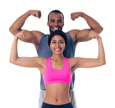 showing muscles: Beautiful Afro American couple in sports clothes is showing muscles, looking at camera and smiling, standing one by one, isolated on white background