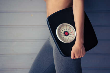 Cropped image of beautiful Afro American sportswoman holding weigh scales, on gray background Stock Photo