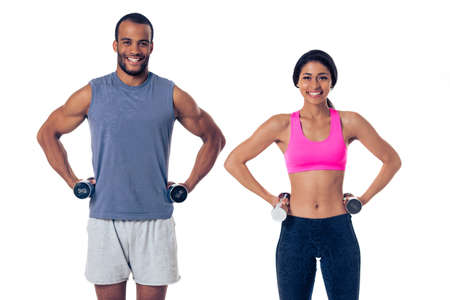 Beautiful Afro American couple in sports clothes is holding dumbbells, looking at camera and smiling, standing akimbo, isolated on white background Stock Photo