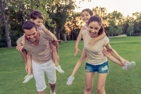 mother love: Beautiful happy family is smiling while having fun outdoors, kids are sitting pickaback Stock Photo