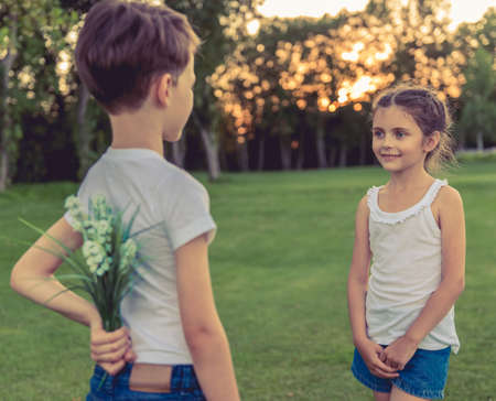 wooing: Little boy is holding flowers behind his back for beautiful little girl, she is looking at him and smiling