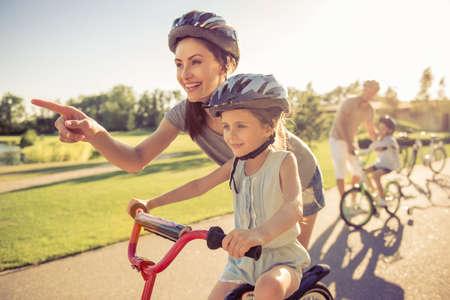 행복한 가족 자전거를 야외에서 타고 웃고. 부모는 자녀를 가르치고 있습니다. 엄마와 딸 포 그라운드에서
