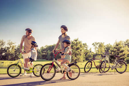 Happy family is riding bikes outdoors and smiling. Parents are teaching their children Foto de archivo