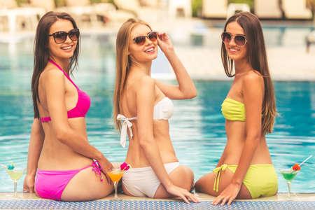 Mooie meisjes in zwemkleding en zonnebrillen zijn op zoek naar de camera en glimlachen terwijl zonnen bij het zwembad