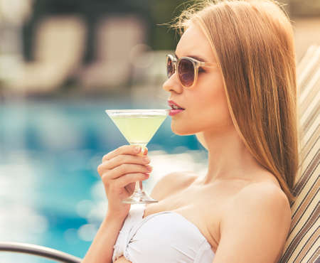longue: Attractive girl in white swimwear and sun glasses is drinking a cocktail and sunbathing while lying on the chaise longue near the pool