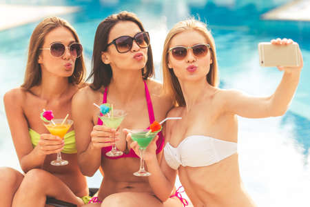 Beautiful girls in swimwear and sun glasses are making selfie using a smart phone, drinking cocktails and sending air kisses while sunbathing near the pool