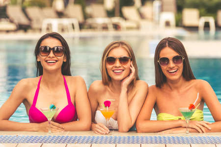 Beautiful girls in swimwear and sun glasses are drinking cocktails, looking at camera and smiling while swimming in the pool