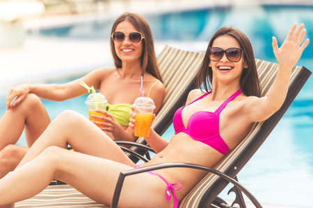 longue: Beautiful girls in swimwear and sun glasses are drinking juice, looking at camera and smiling while sunbathing on the chaise longue near the pool. One girl is waving