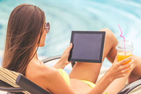 Back view of pretty girl in green swimwear and sun glasses sunbathing, drinking juice and using a digital tablet while lying on the chaise longue near the pool