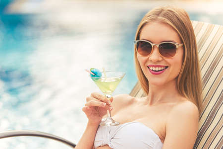 longue: Attractive girl in white swimwear and sun glasses is holding a cocktail, looking at camera and smiling while lying on the chaise longue near the pool