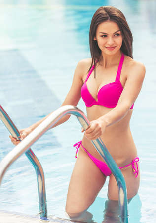 Beautiful girl in pink swimwear is going out of the pool, looking away and smiling