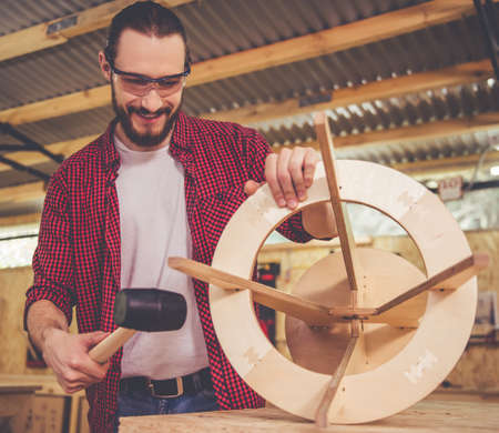 protective glasses: Handsome carpenter in protective glasses is smiling while working with wood and a hammer in the workshop