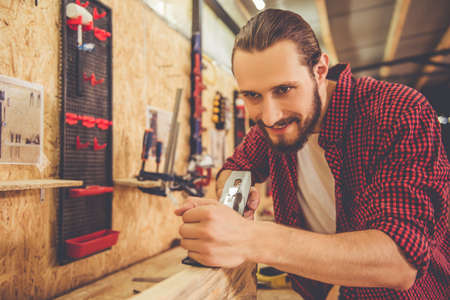 Handsome carpenter is smiling while working with wood and carpenters plane in the workshop Stock Photo