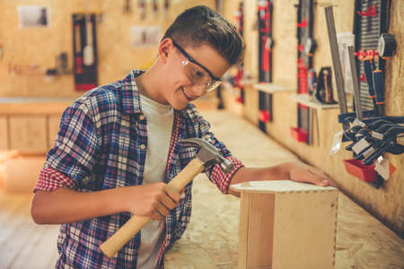 Handsome teenage carpenter in protective glasses is smiling while working with wood and a hammer in the workshop Stock Photo