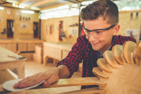 Handsome teenage carpenter in protective glasses is smiling while working with wood and sandpaper in the workshop Stock Photo