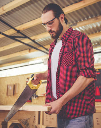 protective glasses: Handsome carpenter in protective glasses is cutting wood using a saw in the workshop