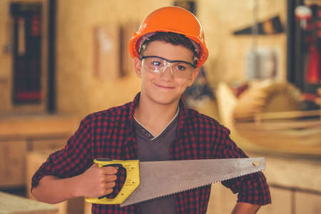 Handsome teenage carpenter in hard hat and protective glasses is holding a saw, looking at camera and smiling while standing in the workshop Stock Photo