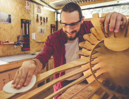 protective glasses: Handsome carpenter in protective glasses is smiling while working with wood and sandpaper in the workshop
