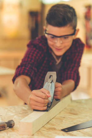 protective glasses: Handsome teenage carpenter in protective glasses is smiling while working with wood and carpenters plane in the studio