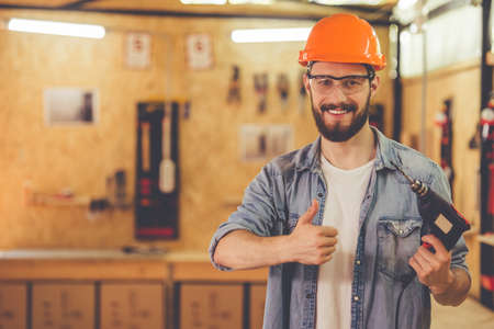 Handsome carpenter in hard hat and protective glasses is holding a drilling machine, showing Ok sign, looking at camera and smiling while standing in the workshop