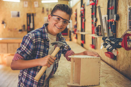 Handsome teenage carpenter in protective glasses is looking at camera and smiling while working with wood and a hammer in the workshop Stock Photo