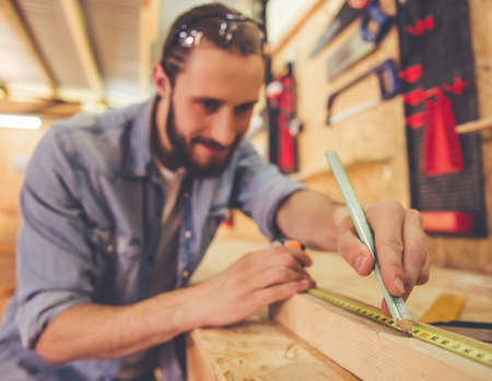 Handsome carpenter in protective glasses is smiling while measuring wood using a tape measure and pencil in the workshop. Tools in focus